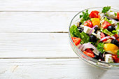 Fresh Greek salad made of cherry tomato, feta, olives, onion and spices. Caesar salad in a glass bowl on wooden table. Healthy organic diet food concept