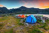 Camping place near alpine lake at sunset, Retezat mountains, Romania