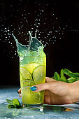 Woman hand holds mojito coctail on dark background with splash