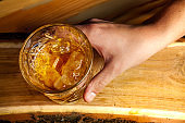 Top view hand holds rum or whiskey glass with ice on a wooden background.