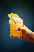 hand holds orange alcohol cocktail with ice, orange and lime on trending blue background. Bar conceptual view.