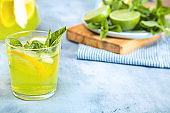 Fresh mojito cocktail on background with wooden board full of lime and mint.