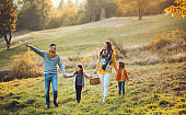 A young family with two small children walking in autumn nature.