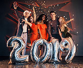 The new 2019 is approaching. A group of merry young multinational people in Santa's hat with silver numbers and throwing confetti at the party. Happy New Year.