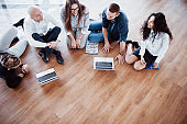 Young creative people in modern office. Group of young business people are working together with laptop. Freelancers sitting on the floor. Cooperation corporate achievement. Teamwork concept