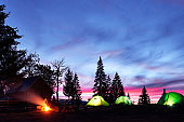 Night camping. Tourist have a rest at a campfire near illuminated tent and wooden house under amazing night sky full of stars and milky way