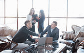 Welcome on board Two handsome men shaking hands with smile at office with their coworkers. Young team of coworkers making great business discussion in modern coworking office. Teamwork people concept