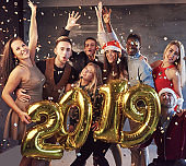 New 2019 Year is coming! Group of cheerful young multiethnic people in Santa hats carrying gold colored numbers and throwing confetti on the party