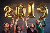 A group of merry young people hold numbers indicating the arrival of a new 2019 year. The party is dedicated to the celebration of the new year. Concepts about youth togetherness lifestyle