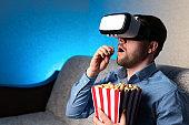 Man in VR headset eating popcorn