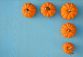 Border of little orange pumpkins on blue