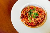 Top view and copy space, spaghetti  Bolognese topped with grated cheese and placed on white dish with wooden background