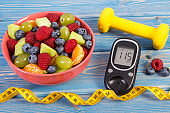 Fruit salad, glucometer, centimeter and dumbbells, diabetes, healthy lifestyle and nutrition concept
