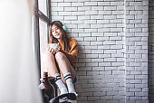 Relaxation Concept. a Happy Young Woman Spending Time to Listening Music and Hot Coffee in Cozy House, Nearby Window, Closed Eyes and Smiling