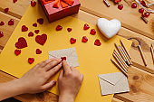 The girl wrote a letter with congratulations and pastes the envelope with a symbol in the form of a heart. Nearby lie various objects symbolizing the event.