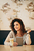 Woman using tablet in cafe.