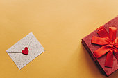 Envelope with a symbol in the form of a red heart and next box with a gift bandaged with a ribbon on a yellow background.