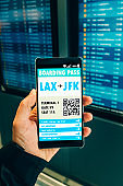 Point of view of boarding pass on mobile phone next to departure board in airport
