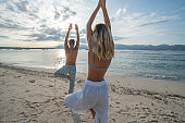 Healthy young couple exercising yoga outdoors on the beach at sunrise in a tropical climate, Bali, Indonesia. People healthy balance concept