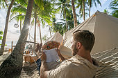 Young man reading book at clamping site, camping in the tropical locations