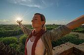 Young woman embracing Bagan temples at sunrise, Myanmar