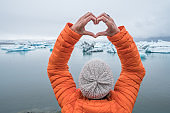 Young woman making heart shape finger frame overhead on glacier lagoon in Iceland