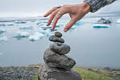 Detail of person stacking rocks by the glacier lagoon in Iceland