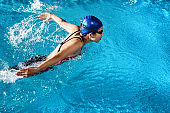 Swimmers are swimming 'butterfly' poolside at night.