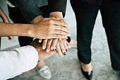 Close up of young business people putting and join their hands together. Team with stack of hands showing unity, collaboration and teamwork. Business teamwork concept.