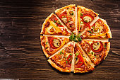 Pizza with champignon, tomatoes and salami on wooden background
