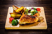 Roast chicken leg with fried potatoes and fresh vegetables