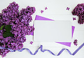 Lilac flowers with greeting card on a table