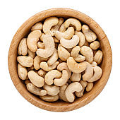 Raw cashew nuts in wooden bowl isolated on white. Top view.