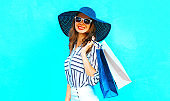 Elegant young smiling woman wearing a shopping bags, straw hat, white pants over colorful blue background posing in the city