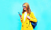 Fashion beautiful smiling woman using smartphone on colorful blue background