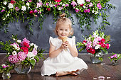 Little girl eats ice cream and laughs. A flower decor in an interior. Portrait of the emotional lovely girl