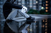 Reflection of mystery hoodie man with black mask holding white mask sitting in the rain on rooftop of abandoned building. Bipolar disorder or Major depressive disorder. Depression concept