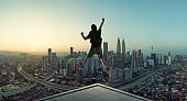 Young man jumping on rooftop