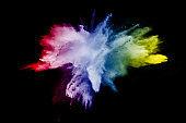 Multi color particles explosion on black background. Colorful dust splatter on dark background.