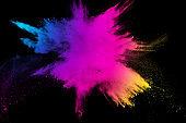 Multi color powder explosion isolated on black background. Colored dust splash cloud on black background. Launched colorful particles on background. Painted Holi.