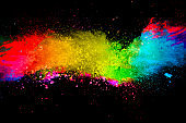 Multi color powder explosion isolated on black background. Colored dust splash cloud on black background. Launched colorful particles on background. Painted Holi.