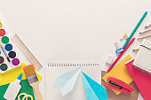 Top view over a school supplies as calculator, rulers, tapes, paper clips, notebooks and paper planes placed in a circle on a white background. Back to school concept. Office supplies flat lay