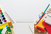 Top view over a school supplies as calculator, rulers, tapes, paper clips, notebooks and scissors placed in a circle on a white background. Back to school concept. Office supplies flat lay