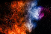 Multi color particles explosion on black background. Colorful dust splatter on dark background.