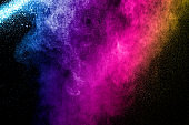 Abstract multi color powder explosion on black background.  Freeze motion of color dust  particles splash. Painted Holi.