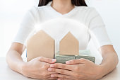 Woman hand holding and protect home and money with barrier for insurance concept