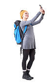 Relaxed happy traveling young woman with rucksack taking selfie with smartphone.
