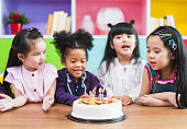 Group diversity kids blowing birth day cake.