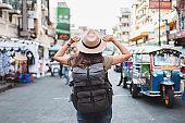 Back view Asian woman tourist backpacker travel in Khao San road, Bangkok, Thailand