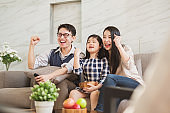 Happy Asian family lifestyle enjoy watching TV at home